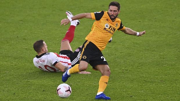 Sheffield United's Billy Sharp falls after competing for the ball with Wolverhampton Wanderers' Joao Moutinho during the English League Cup soccer match between Sheffield United and Wolves at Bramall Lane stadium in Sheffield, England, Monday, Sept. 14, 2020. (Laurence Griffiths/Pool via AP)