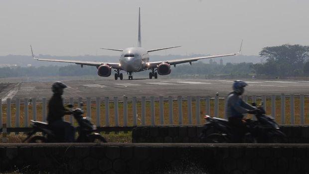 Sejumlah pengendara motor melintas dengan latar belakang pesawat komersial yang akan lepas landas di Bandara Adi Soemarmo, Boyolali, Jawa Tengah, Rabu (16/9/2020). Berdasarkan data PT Angkasa Pura I Bandara Adi Soemarmo, pengguna jasa penerbangan saat pandemi COVID-19 melalui bandara tersebut mulai naik dari bulan Mei sebanyak 17 ribu penumpang naik menjadi 34 ribu penumpang pada bulan Agustus. ANTARA FOTO/Aloysius Jarot Nugroho/aww.