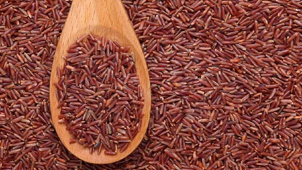 Red rice in a wooden spoon on red rice background.Please see: