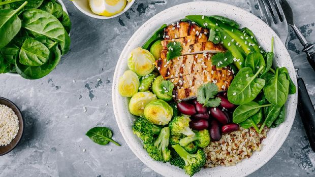 Healthy buddha bowl lunch with grilled chicken, quinoa, spinach, avocado, brussels sprouts, broccoli, red beans with sesame seeds on dark gray background. Top view.