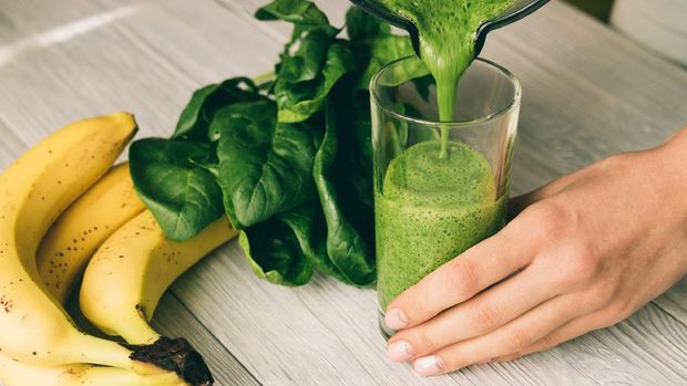 Female hand pours a smoothie of banana and spinach in glass on a wooden table