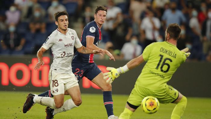 Metzs goalkeeper Alexandre Oukidja, right, makes a save against PSGs Julian Draxler, center, during the French League One soccer match between Paris Saint-Germain and Metz at the Parc des Princes in Paris, France, Wednesday, Sept.16, 2020. (AP Photo/Francois Mori)