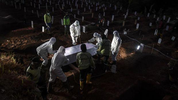 Petugas penggali makam jenazah COVID-19 menurunkan peti ke dalam liang lahat di komplek pemakaman Pondok Ranggon. ANTARA FOTO/Muhammad Adimaja