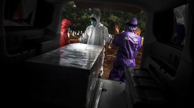 Petugas penggali makam jenazah COVID-19 bersiap menurunkan peti di komplek pemakaman Pondok Ranggon. ANTARA FOTO/Muhammad Adimaja