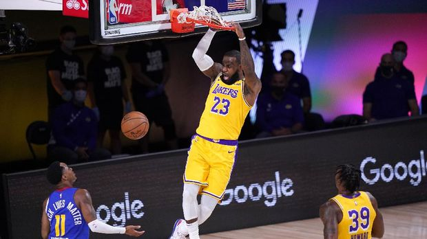 Denver Nuggets guard Monte Morris (11) and Los Angeles Lakers' Dwight Howard (39) look on as LeBron James (23) dunks in the first half an NBA conference final playoff basketball game Friday, Sept. 18, 2020, in Lake Buena Vista, Fla. (AP Photo/Mark J. Terrill)