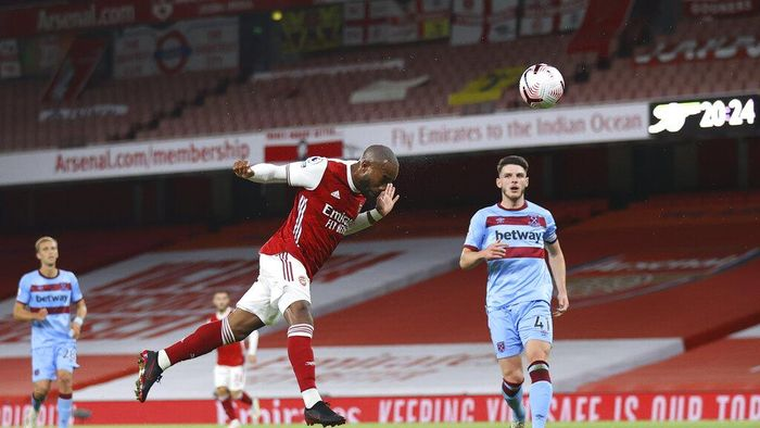 Arsenals Alexandre Lacazette scores the opening goal during the English Premier League soccer match between Arsenal and West Ham at the Emirates Stadium in London, England, Saturday, Sept. 19, 2020. (Julian Finney/Pool via AP)