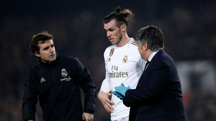 BARCELONA, SPAIN - DECEMBER 18:  Gareth Bale of Real Madrid receives medical attention during the Liga match between FC Barcelona and Real Madrid CF at Camp Nou on December 18, 2019 in Barcelona, Spain. (Photo by Eric Alonso/Getty Images)