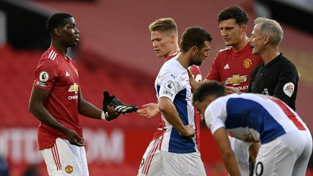 Manchester United's French midfielder Paul Pogba, center, holds his boot as he talks to Referee Martin Atkinson after he went down in the box during the English Premier League soccer match between Manchester United and Crystal Palace at the Old Trafford stadium in Manchester, England, Saturday, Sept. 19, 2020. (Shaun Botterill/Pool via AP)