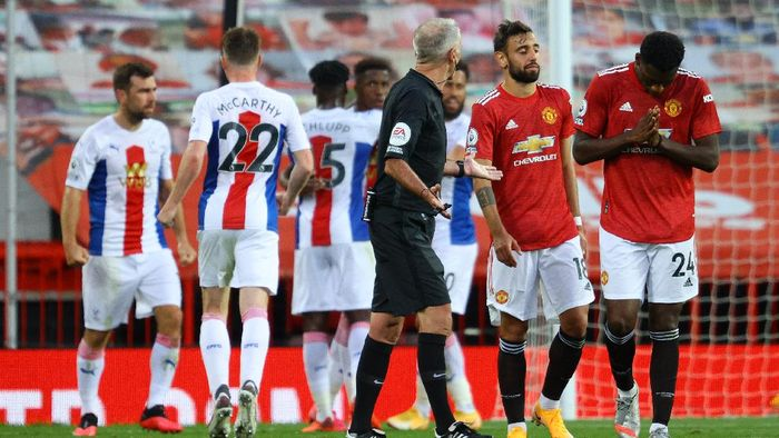 MANCHESTER, ENGLAND - SEPTEMBER 19: Referee Martin Atkinson speaks with Bruno Fernandes and Tim Fosu-Mensah of Manchester United after Manchester United concede a second goal during the Premier League match between Manchester United and Crystal Palace at Old Trafford on September 19, 2020 in Manchester, England. (Photo by Richard Heathcote/Getty Images )