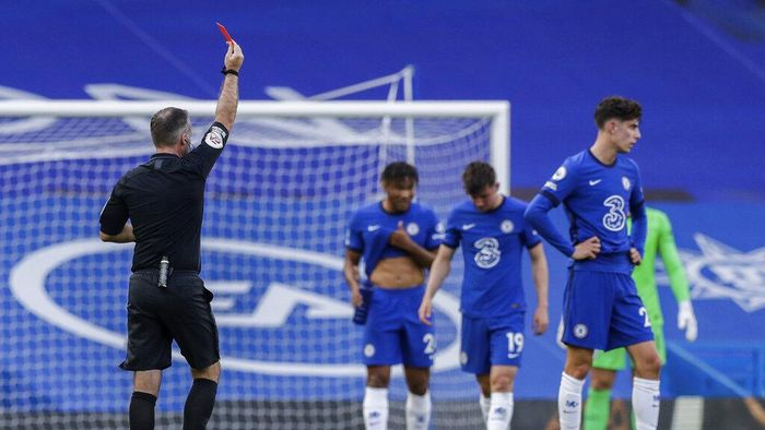 Referee Paul Tierney shows a red card to Chelseas Andreas Christensen, not pictured, during the English Premier League soccer match between Chelsea and Liverpool at Stamford Bridge Stadium, Sunday, Sept. 20, 2020. (AP Photo/Matt Dunham, Pool)