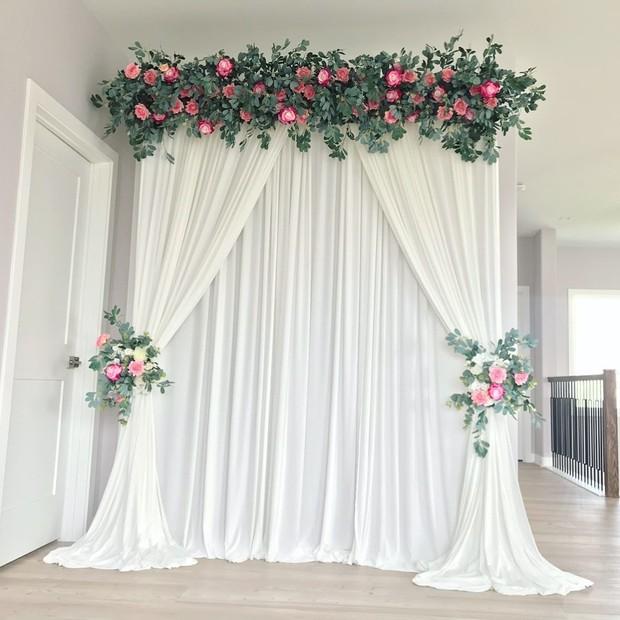 Backdrop floral dengan nuansa putih menjadi pilihan yang ciamik