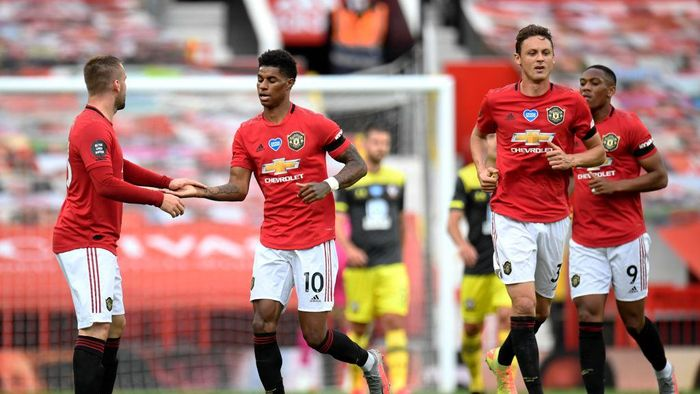 MANCHESTER, ENGLAND - JULY 13: Marcus Rashford of Manchester United celebrates with teammate Luke Shaw of Manchester United after scoring his teams first goal during the Premier League match between Manchester United and Southampton FC at Old Trafford on July 13, 2020 in Manchester, England. Football Stadiums around Europe remain empty due to the Coronavirus Pandemic as Government social distancing laws prohibit fans inside venues resulting in all fixtures being played behind closed doors. (Photo by Peter Powell/Pool via Getty Images)