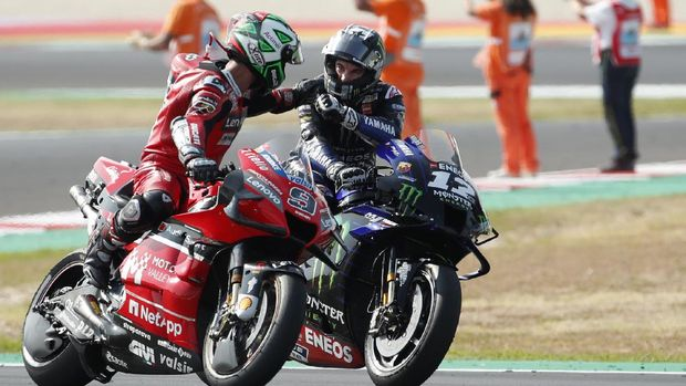 MotoGP rider Maverick Vinales of Spain is congratulated by Danilo Petrucci of Italy, left, after winning the Emilia Romagna Motorcycle Grand Prix at the Misano circuit in Misano Adriatico, Italy, Sunday, Sept. 20, 2020. (AP Photo/Antonio Calanni)