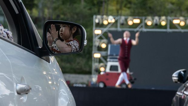 In a photo taken on September 19, 2020, a spectator watches from a car as a performer puts on a display at a drive-in circus performance in Seoul. - The annual circus -- usually held in May -- was pushed back twice this year because of the virus until organisers turned it into a drive-in event. (Photo by - / AFP)