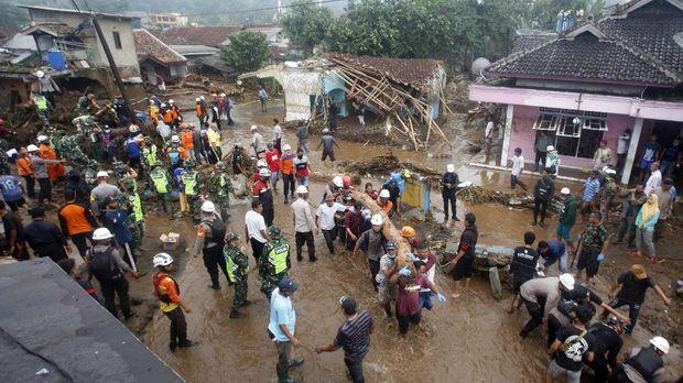 Sejumlah relawan gabungan mengevakuasi material kayu yang terbawa pasca  banjir bandang di  Kampung Cibuntu, Desa Pasawahan, Kecamatan Cicurug, Sukabumi, Jawa Barat, Selasa (22/9/2020). Data sementara yang dikeluarkan Badan Penanggulangan Bencana Daerah Kabupaten Sukabumi, Jawa Barat, dampak akibat banjir bandang yang terjadi di Kecamatan Cicurug, Senin (21/9), mengakibatkan 12 rumah hanyut dan 85 rumah terendam. ANTARA FOTO/Yulius Satria Wijaya/foc.