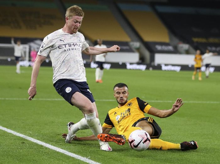 Manchester Citys Kevin De Bruyne, left, reacts as he is fouled by Wolverhampton Wanderers Romain Saiss during the English Premier League soccer match between Wolverhampton Wanderers and Manchester City at Molineux Stadium in Wolverhampton, England, Monday, Sept. 21, 2020. (Nick Potts/Pool via AP)