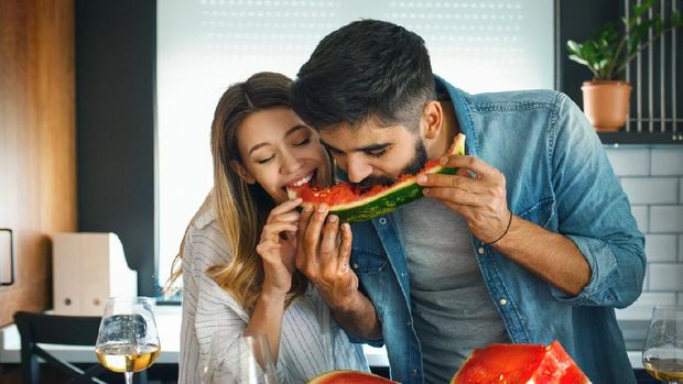 Closeup front view of a mid 20's couple sharing a watermelon in a kitchen. They are biting the same slice and laughing, having some white wine as well