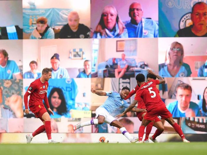 MANCHESTER, ENGLAND - JULY 02: Raheem Sterling of Manchester City is fouled in the penalty area by Joe Gomez of Liverpool as fans watch on the big screen during the Premier League match between Manchester City and Liverpool FC at Etihad Stadium on July 02, 2020 in Manchester, England. Football Stadiums around Europe remain empty due to the Coronavirus Pandemic as Government social distancing laws prohibit fans inside venues resulting in games being played behind closed doors. (Photo by Laurence Griffiths/Getty Images)