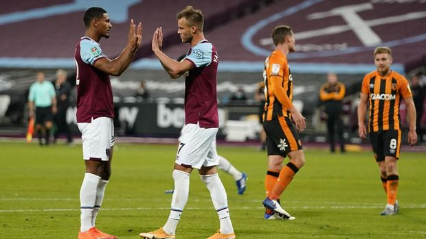 West Ham's Andriy Yarmolenko, second right, celebrates with West Ham's Sebastien Haller after scoring his side's third goal from the penalty spot during the English League Cup soccer match between West Ham and Hull City at the London Stadium in London, Tuesday, Sept. 22, 2020. (Will Oliver/Pool via AP)