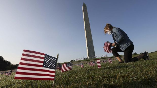 WASHINGTON, DC - SEPTEMBER 22: Carmen Wilke places flags at a COVID Memorial Project install of 20,000 American flags on the National Mall as the United States crosses the 200,000 lives lost in the COVID-19 pandemic September 22, 2020 in Washington, DC. The flags are displayed on the grounds of the Washington Monument facing the White House.   Win McNamee/Getty Images/AFP