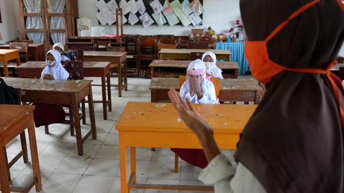 Guru mengajar anak berdoa pada hari pertama proses belajar mengajar di Sekolah Dasar Negeri Garot, Desa Ketapang, Kecamatan Darui Imarah, Kabapaten Aceh Besar, Aceh, Rabu (23/9/2020). Sebagian sekolah di daerah itu mulai melaksanakan aktivitas belajar mengajar tatap muka dengan membatasi jumlah murid dan tetap menerapkan protokol kesehatan guna mencegah penyebaran COVID-19. ANTARA FOTO/Ampelsa/aww.