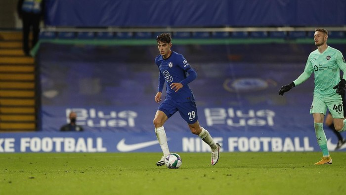 Chelseas Kai Havertz, left, dribbles past Barnsleys goalkeeper Brad Collins, top score his teams third goal during the English League Cup third round soccer match between Chelsea and Barnsley at Stamford Bridge in London, Wednesday, Sept. 23, 2020. (AP Photo/Alastair Grant)