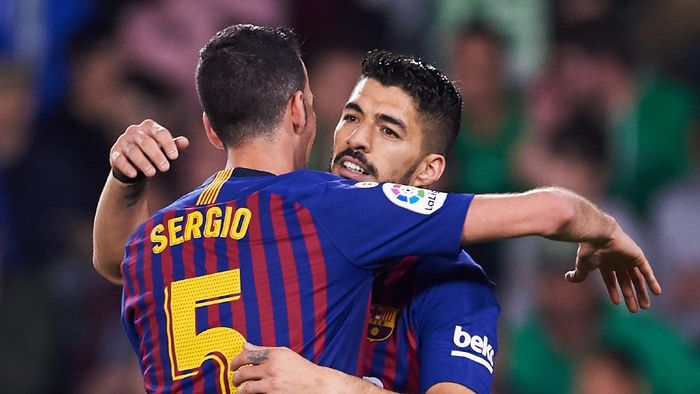 SEVILLE, SPAIN - MARCH 17: Luis Suarez of FC Barcelona celebrates with his teammates Sergio Busquets of FC Barcelona after scoring his teams third goal during the La Liga match between Real Betis Balompie and FC Barcelona at Estadio Benito Villamarin on March 17, 2019 in Seville, Spain. (Photo by Aitor Alcalde/Getty Images)