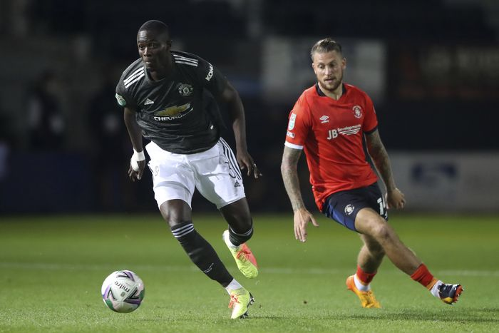 Manchester Uniteds Eric Bailly, left, runs with the ball past Luton Towns George Moncur during the English League Cup 3rd round soccer match between Luton Town and Manchester United, Tuesday, Sept. 22, 2020, at Kenilworth Road in Luton, England. (Nick Potts/Pool via AP)