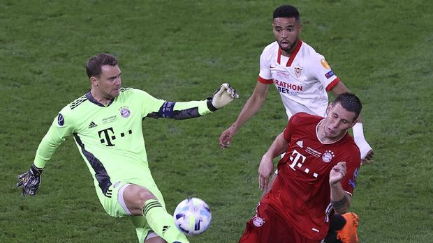 Bayern's goalkeeper Manuel Neuer kicks the ball next to Bayern's Niklas Suele during the UEFA Super Cup soccer match between Bayern Munich and Sevilla at the Puskas Arena in Budapest, Hungary, Thursday, Sept. 24, 2020. (Laszlo Szirtesi/Pool via AP)