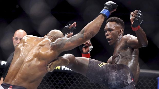 FILE- In this March 7, 2020, file photo, UFC middleweight champion Israel Adesanya, right, of Nigeria, kicks challenger Yoel Romero, of Cuba, during the second round of their UFC 248 fight at the T-Mobile Arena in Las Vegas. Israel Adesanya returns to the UFC cage this weekend to defend his middleweight title against Paulo Costa in the main event of UFC 253.  (L.E. Baskow/Las Vegas Review-Journal via AP, File)