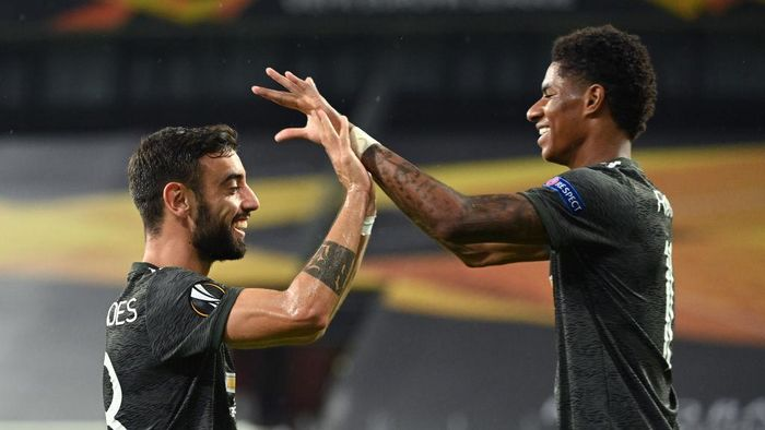 COLOGNE, GERMANY - AUGUST 16: Bruno Fernandes of Manchester United  celebrates with Marcus Rashford  after scoring his teams first goal from the penalty spot during the UEFA Europa League Semi Final between Sevilla and Manchester United at RheinEnergieStadion on August 16, 2020 in Cologne, Germany. (Photo by Ina Fassbender/Pool via Getty Images)