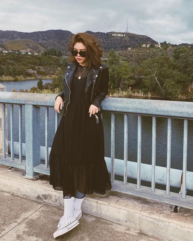 Dress hitam diberi blazer kulit semakin klop dengan sneakers