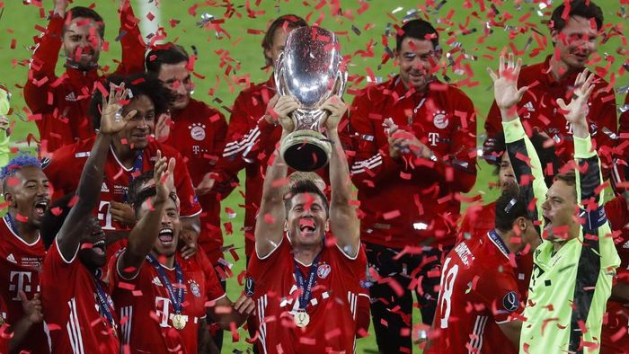 Bayern Munichs Polish forward Robert Lewandowski (C) raises the trophy with his teammates after the UEFA Super Cup football match between FC Bayern Munich and Sevilla FC at the Puskas Arena in Budapest, Hungary on September 24, 2020. (Photo by Laszlo Balogh / POOL / AFP)