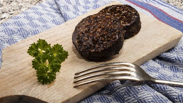 grilled irish black pudding made with oatmeal on a wooden board with knife and parsley