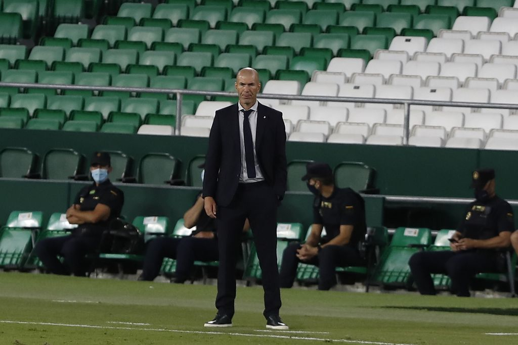 Real Madrid's head coach Zinedine Zidane loos on during the Spanish La Liga soccer match between Betis and Real Madrid at the at the Benito Villamarin stadium in Seville, Spain, Saturday, Sept. 26, 2020. (AP Photo/Angel Fernandez)