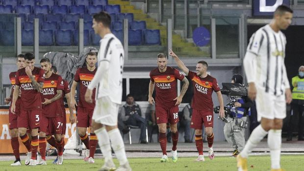 Roma's Jordan Veretout, right, celebrates after scoring his side's second goal during the Italian Serie A soccer match between Roma and Juventus at Rome's Olympic stadium, Sunday, Sept. 27, 2020. (AP Photo/Gregorio Borgia)