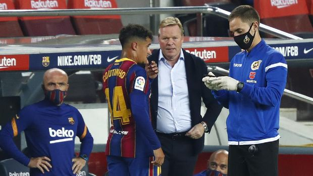 Barcelona's head coach Ronald Koeman speaks with Barcelona's Philippe Coutinho during the Spanish La Liga soccer match between FC Barcelona and Villareal FC at the Camp Nou stadium in Barcelona, Spain, Sunday, Sept. 27, 2020. (AP Photo/Joan Monfort)