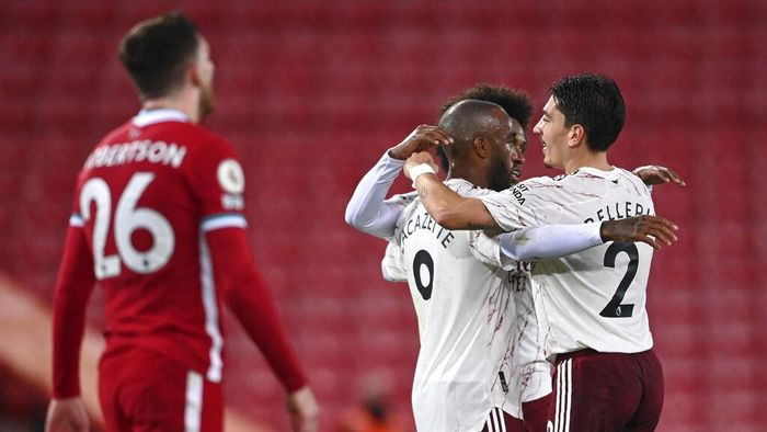 Arsenals Alexandre Lacazette, centre, is congratulated by teammates after scoring his teams first goal during the English Premier League soccer match between Liverpool and Arsenal at Anfield in Liverpool, England, Monday, Sept. 28, 2020. (Laurence Griffiths/Pool via AP)