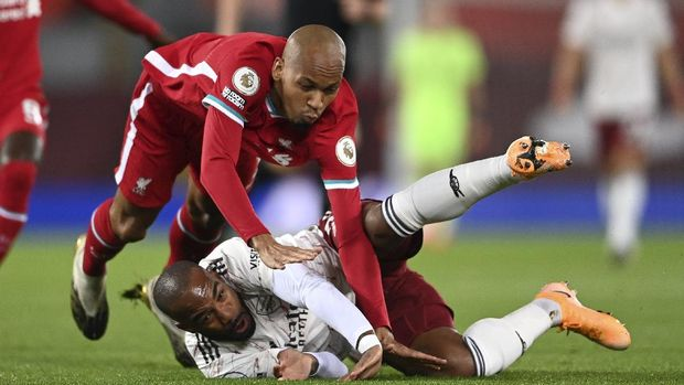 Arsenal's Alexandre Lacazette and Liverpool's Fabinho, left, fall during the English Premier League soccer match between Liverpool and Arsenal at Anfield in Liverpool, England, Monday, Sept. 28, 2020. (Laurence Griffiths/Pool via AP)