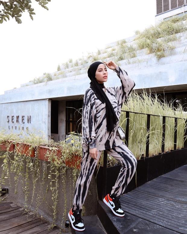 Potret penampilan Aghnia Punjabi dalam busana monokrom yang terlihat modis.