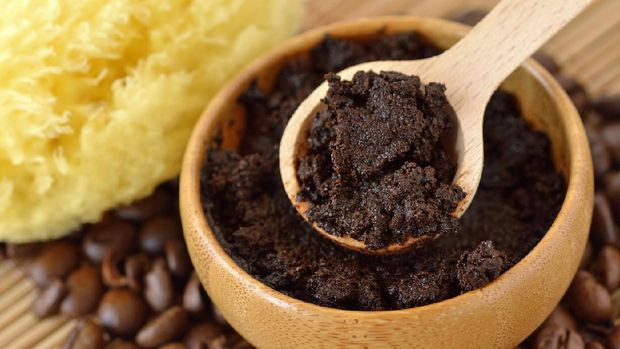 Homemade coffee scrub face mask in wooden bowl with spoon on coffee beans