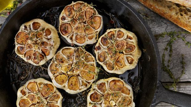 Roasted Garlic with Salt, Pepper, Thyme and Olive Oil in a Cast Iron Skillet