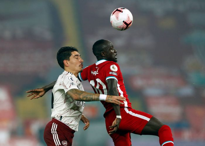 LIVERPOOL, ENGLAND - SEPTEMBER 28: Sadio Mane of Liverpool wins a header in front of Hector Bellerin of Arsenal during the Premier League match between Liverpool and Arsenal at Anfield on September 28, 2020 in Liverpool, England. Sporting stadiums around the UK remain under strict restrictions due to the Coronavirus Pandemic as Government social distancing laws prohibit fans inside venues resulting in games being played behind closed doors. (Photo by Jason Cairnduff - Pool/Getty Images)