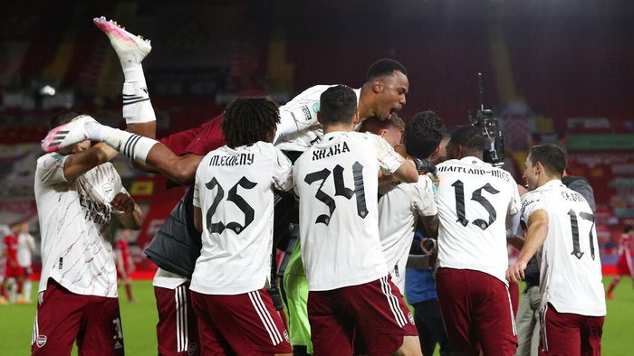 Arsenal players celebrate after winning the English League Cup fourth round soccer match between Liverpool and Arsenal at Anfield, Liverpool, England, Thursday, Oct. 1, 2020. Arsenal defeated Liverpool 5-4 in penalties. (Peter Byrne/Pool via AP)