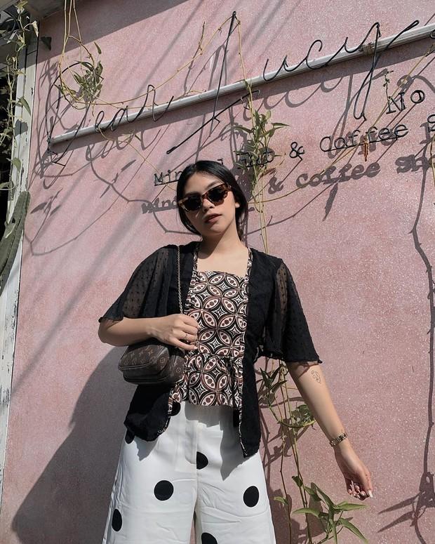 . Dia memadukan atasan batik yang modern dengan celana putih motif polkadot.