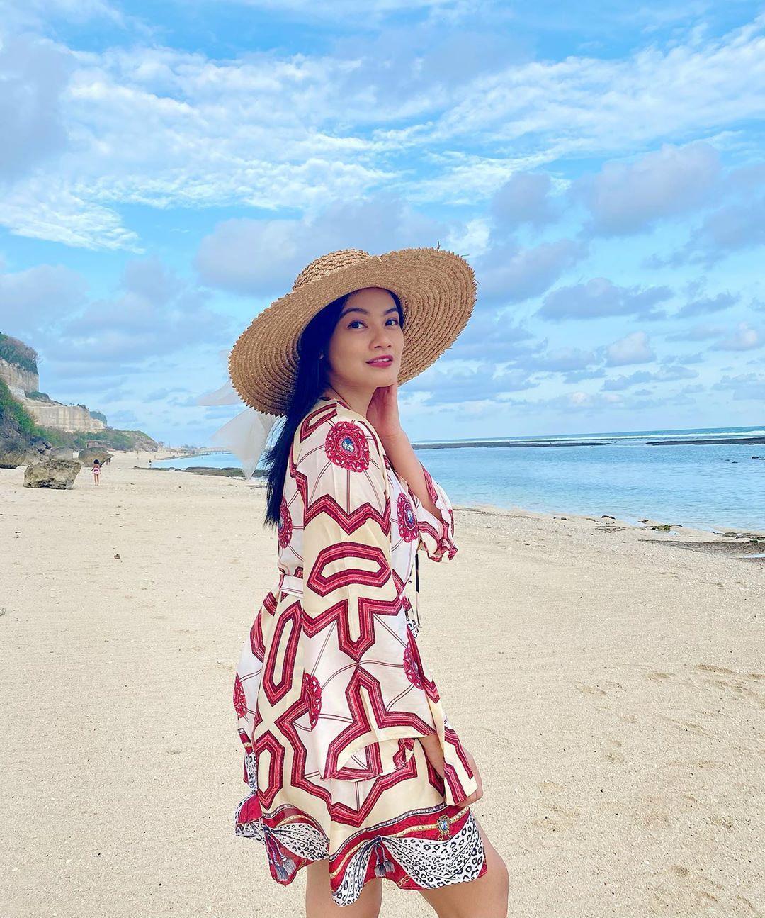 Menikmati pantai yang sepi, pasir pantai yang lembut, pemandangan laut yang indah menjadi aktivitas menyenangkan Titi Kamal