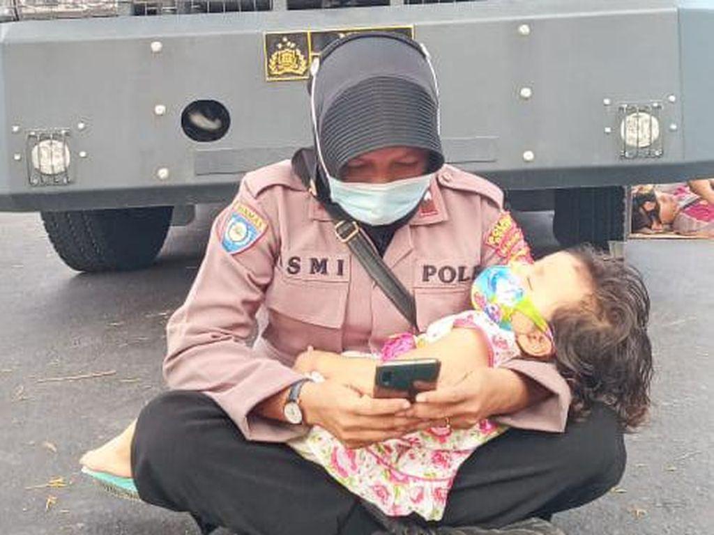 Viral Foto Polwan Gendong Anak Jaga Aksi Demo Pilkada di Dompu