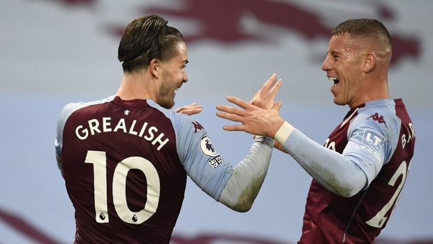 Aston Villa's Jack Grealish, left, celebrates after scoring his side's sixth goal with Aston Villa's Ross Barkley during the English Premier League soccer match between Aston Villa and Liverpool at the Villa Park stadium in Birmingham, England, Sunday, Oct. 4, 2020. (Peter Powell/Pool via AP)
