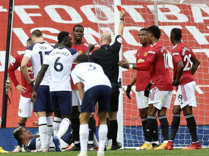 Referee Anthony Taylor shows a red card to Manchester Uniteds Anthony Martial, 3rd right, during the English Premier League soccer match between Manchester United and Tottenham Hotspur at Old Trafford in Manchester, England, Sunday, Oct. 4, 2020. (Carl Recine/Pool via AP)
