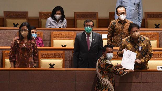 Menko Perekonomian Airlangga Hartarto (kanan) didampingi Menkumham Yasonna Laoly (kedua kiri) dan Menteri Keuangan Sri Mulyani (kiri) menerima laporan akhir dari Ketua Badan Legislasi DPR  Supratman Andi (bawah) saat pembahasan tingkat II RUU Cipta Kerja pada Rapat Paripurna DPR di Kompleks Parlemen, Jakarta, Senin (5/10/2020). ANTARA FOTO/Hafidz Mubarak A/pras.